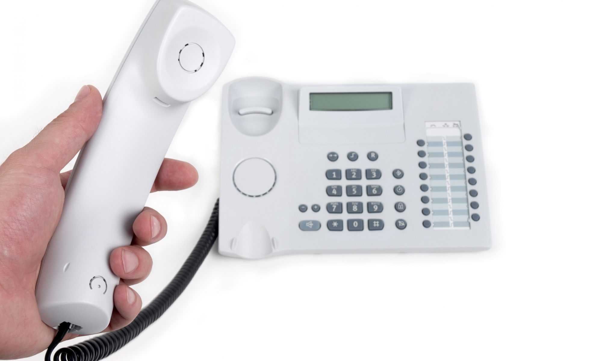 Hand holding a telephone receiver ready to make a call